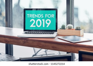 Trends for 2019 word in laptop computer screen with tablet on wood stood table in at window with blur background,Digital Business or marketing trending.