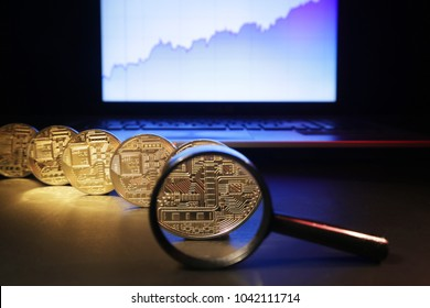 Trends and novelties in the ICO market. A magnifying glass, gold coins of electronic currency and a growing quotation chart symbolize the trends in the Initial coin offering market.
