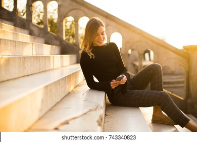 Trendu young woman with mobile phone sitting at stairs outdoor