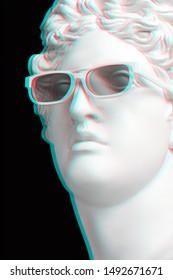 Trendy 3D effect. Statue. Gypsum statue of Apollo's head. Man. Creative. Plaster statue of Apollo's white sunglasses. Head. Sculpture. 3D
