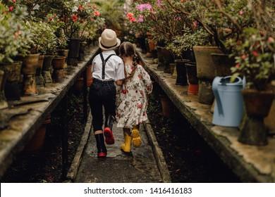 Trendy Adorable Boy and Girl Running in Greenhouse. Kaukasische Kleine Kinder in Gummi Stiefeln Wandern in Blumentopf Glasshouse Back View. Hemd mit Kid-Tragen, Ameisen mit Brasen. Mädchen in gedrucktem Kleid
