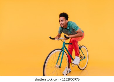 Trendy african man in white sneakers posing emotionally on bike. Indoor portrait of enthusiastic sportive guy sitting on bicycle.