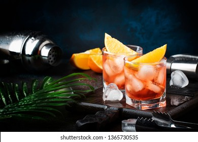 Trendy alcoholic cocktail Negroni with dry gin, red vermouth and red bitter, orange slice and ice cubes. Brown bar counter background, bar tools, night mood, copy space, selective focus