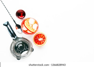 Trendy alcoholic cocktail Negroni with dry gin, red vermouth and red bitter, orange slice and ice cubes. White background, bar tools, top view, copy space