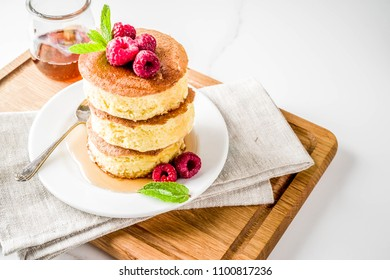 Trendy asian food, Fluffy Japan souffle pancakes, hotcakes with maple syrup and raspberry light concrete background copy space