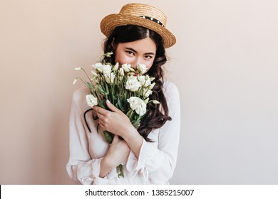 Trendy asian girl sniffing flowers. Romantic brunette young woman holding bouquet of white eustomas.