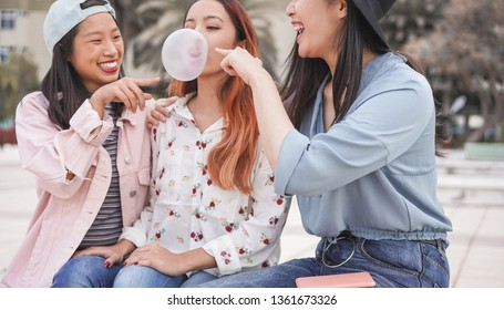 Trendy asian girls having fun together outdoor - Young women friends playing with bubble gum - Trends, youth, millennial generation and friendship concept - Focus on right person mouth
