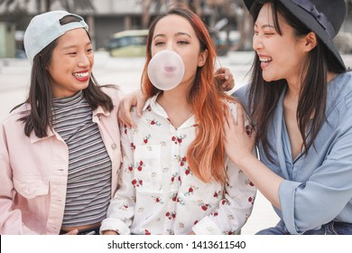 Trendy asian girls having fun together outdoor - Young women friends playing with bubble gum - Trends, youth, millennial generation and friendship concept - Focus on center female face
