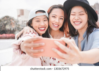 Trendy asian girls making video story for social network app outdoor - Young women friends having fun taking selfie - New technology trends and friendship concept - Focus on faces