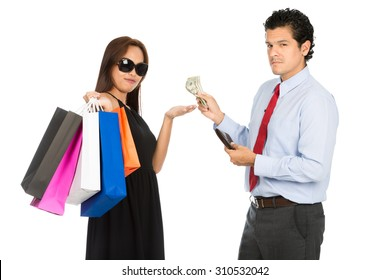 A trendy Asian woman shopaholic with black dress, sunglasses and department store bags accepts money from her wealthy husband looking at camera. H