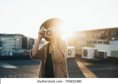 Trendy and attractive beautiful woman with analog vintage film camera makes photos on rooftop at sunset time, creates content for social media channels and applications, popular influencer
