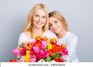 Trendy attractive cheerful mother and daughter enjoying holiday together having big flawless seasonal colorful bouquet of tulips, comfort pleasure joy enjoyment concept isolated on grey background