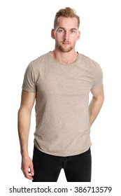 A trendy and attractive man in his 20s wearing black jeans and a tan t shirt standing against a white background in a studio.