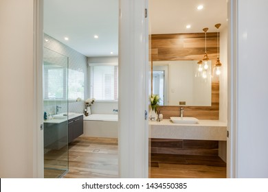 Trendy bathroom with great interior with a partition drawn with a sink with contemporary lighting and planters decorated on the side.