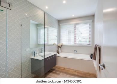 Das trendige Badezimmer ist im Interieur eingerichtet und verfügt über ein elegantes, weißes Waschbecken und eine Badewanne sowie eine Glaswand.