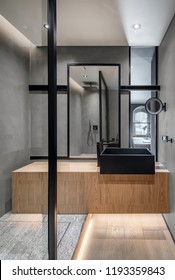 Trendy bathroom in a modern style with gray tiled walls. There is a wooden stand with a black sink and a faucet, large mirror, shower, glass partitions, small round mirror, luminous lamps. Vertical.