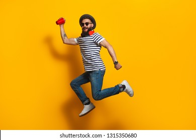 Trendy bearded hipster man in hat and sunglasses holding red cup and jumping up on yellow background
