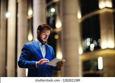 Trendy bearded man browsing tablet standing on street in lights of buildings during nighttime