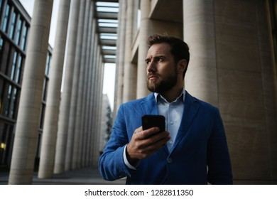 Trendy bearded man in suit holding contemporary smartphone standing on modern urban background