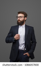 Trendy bearded man wearing elegant modern suit and eyeglasses standing confidently on gray backdrop looking away.