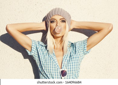 trendy beautiful blonde  in   blue shirt posing on wall background. Blow bubblegum. Outdoors, lifestyle.
