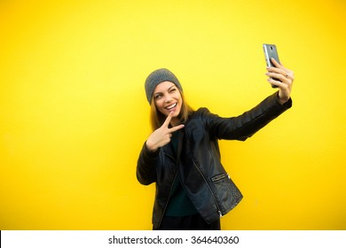 Trendy beautiful cool hipster blond girl wearing a gray hat and black leather jacket taking selfie with mobile phone against a yellow wall. Making peace hand gesture and smiling.