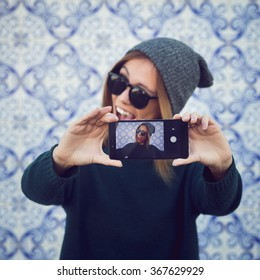 Trendy beautiful cool hipster blond girl wearing a gray hat and glasses against a traditional Spanish or Portuguese tiles azulejo wall taking selfie with smartphone. Edited with filter. Square format.