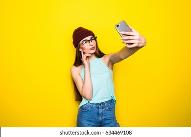 Trendy beautiful hipster girl taking selfie with mobile phone against a yellow wall.