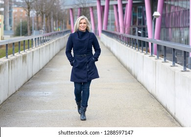 Trendy blond woman in a stylish blue outfit walking along a walkway in town approaching the camera with a friendly smile