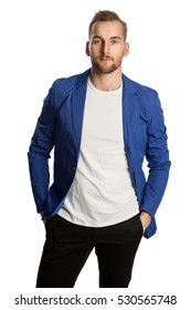 Trendy blonde man wearing a bright blue blazer and dark jeans, standing against a white background smiling towards camera.