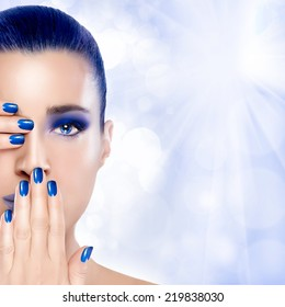Trendy Blue Makeup. Beautiful young woman with hands on her face covering one eye and mouth. Perfect skin. Nail art and makeup concept. High Fashion Portrait with copy space for text