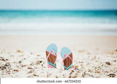 Trendy, blue and pink slippers on white sandy ocean beach.