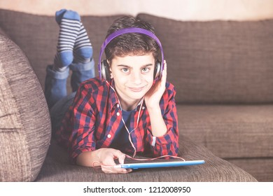 Trendy boy listening to his favorite music using his tablet. Kids and technology concept