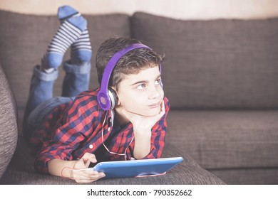 Trendy boy listening to his favorite music using his tablet