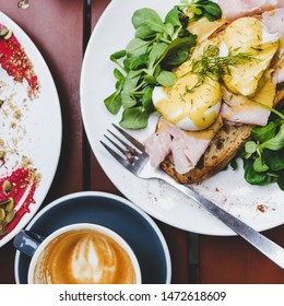 Trendy breakfast set. Flat-lay of poached Eggs Benedict on sourdough bread toast with green salad and pork ham and cup of coffee on cafe table, top view, square crop