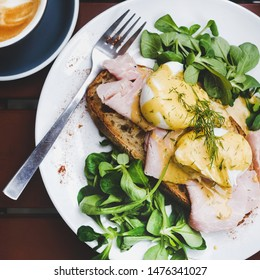 Trendy breakfast set. Flat-lay of poached Eggs Benedict on sourdough bread toast with green salad and pork ham on cafe table, top view, square crop