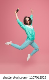 Trendy brunette in blue stylish outfit and sunglasses jumping on pink background holding retro camera in hand