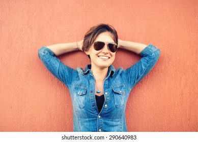 Trendy brunette girl, making face expressions, smiling and laughing against orange background, isolated. Modern lifestyle with beautiful hipster girl with sunglasses