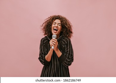 Trendy brunette haired lady in striped stylish black clothes singing with closed eyes and holding microphone on pink backdrop..