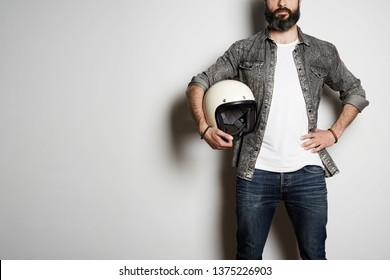 Trendy Brutal bearded male model poses in black jeans shirt and blank white t-shirt premium summer cotton with moto helmet in hands, on white background. Copy paste Advertisement
