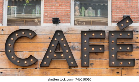 Trendy cafe sign on rustic backboard with windows above illuminated by small hollywood or festoon lights.