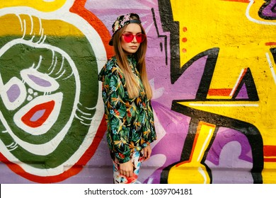 Trendy charming girl in colorful clothes, wearing stylish cap and red eyeglasses, standing with pensive face, posing near the wall with graffiti.