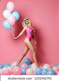 Trendy cheerful blonde woman on birthday party having fun walking with pastel color air balloons looking up happy smiling on pink background