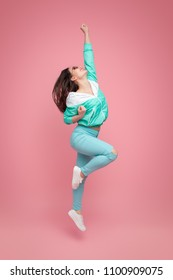 Trendy cheerful woman in blue jumping with hand up and laughing on pink background.