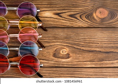 Trendy chic colored generic sunglasses with round lenses arranged as a side border on rustic wood with decorative woodgrain pattern and copy space