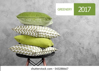 Trendy color concept. Pile of pillows on chair. Word GREENERY 2017 on background