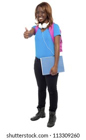Trendy confident college showing thumbs up to camera. Enjoying music through headphones