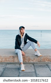 Trendy and cool young female in aviator glasses, baseball cap, sweatpants and hoodie sits on concrete pier next to sea or ocean,poses for camera with model face expression, hip and beautiful empowered
