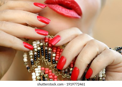 Trendy coral-colored manicure and makeup on a young woman close-up.