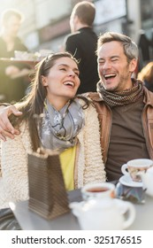 Trendy couple having fun and sitting at a terrace in the city center. The woman is wearing a woolen coat and a scarf The grey hair man has a beard and a leather coat A shopping bag is on the bar table